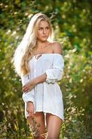 sensuell ung blond kvinna med kort tröja i skogen foto