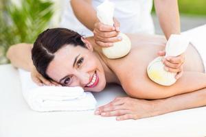 brunett med massage med växtbaserade kompresser foto