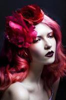 vacker flicka med rosa hår, stor rosblomma i henne foto