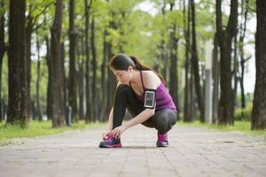 asiatisk ung kvinna löpare knyta skosnören hälsosam livsstil foto