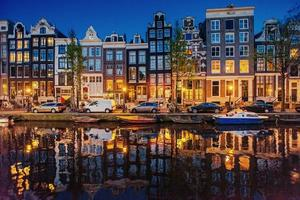 vacker natt i Amsterdam, belysning av byggnader och båt foto
