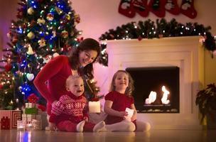 mamma och söta barn hemma på julafton foto