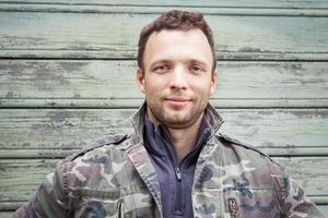 ung kaukasisk man i kamouflage. utomhus porträtt foto