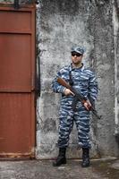 kaukasiska militär man håller gevär i stadskrig foto