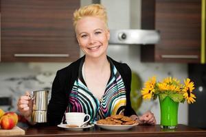 vacker ung kaukasisk blond kvinna matlagning espressokaffe foto