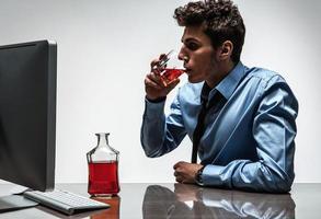 ung berusad kaukasisk affärsman med flaska alkohol foto