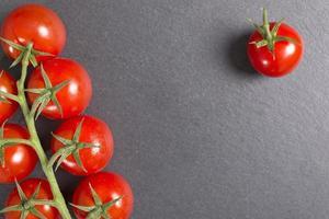 färska tomater på svart skiffer foto