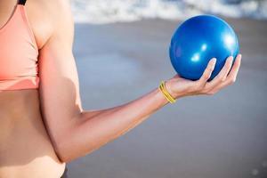 vacker kaukasisk kvinna som tränar med blå boll på stranden foto