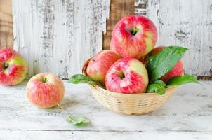 röda äpplen i en korg foto