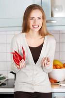 vacker kaukasisk kvinna håller chilipeppar och vitlök. foto