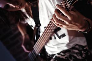 tonårs kaukasiska puk tjej spelar elektrisk basgitarr närbild foto