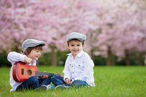 två bedårande kaukasiska pojkar i en blommande körsbärsträdgård