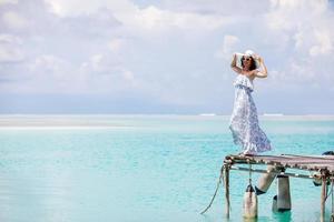 kaukasisk kvinna tar vila på träpiren till Indiska havet foto