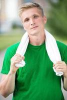 trött man efter träningstid och träning. med vit handduk foto