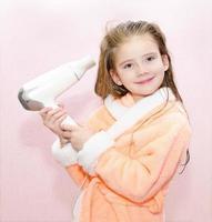 söt leende liten flicka torkar hår foto