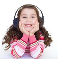 vacker söt glad liten flicka med hörlurar. foto