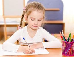 söt liten flicka skriver vid skrivbordet foto