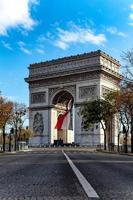 franska flaggan under Arc de Triomphe i Paris foto