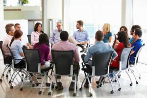 multikulturell kontorspersonal som sitter och möter tillsammans foto