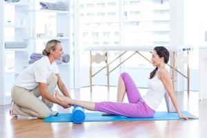tränare som arbetar med kvinnan på träningsmatta foto