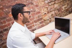 koncentrerad affärsman som använder bärbar dator vid skrivbordet foto