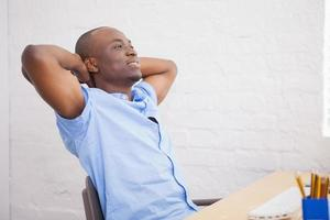 affärsman som sitter med händerna bakom huvudet vid skrivbordet foto