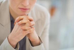 närbild på tankeväckande affärskvinna som sitter vid skrivbordet foto