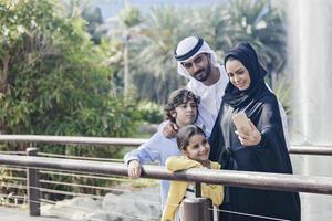 Mellanösternsfamiljen tar selfie utomhus foto
