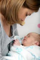 litet nyfött pojke i mammors armar foto