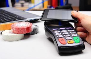 betalar med nfc-teknik på mobiltelefon foto