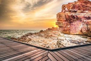 trä gångbro vid solnedgången foto