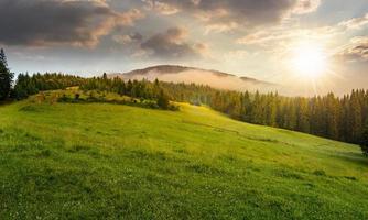 dimma runt bergstoppen vid solnedgången foto