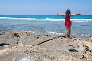 liten flicka som tycker om i en vind från havet foto