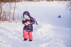 liten bedårande glad tjej som tycker om snö solig vinterdag foto