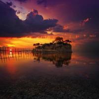 vacker solnedgång med stenig ö foto