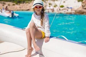 porträtt av liten flicka som tycker om att segla på stor båt foto