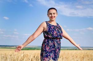 kvinna stående njuter av solen i ett vetefält