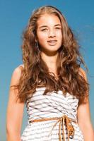 glad vacker flicka med långt brunt hår njuter utomhus. foto