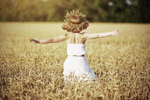 glad tjej som njuter av livet i vetefält på sommaren
