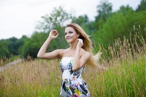 skönhet flicka utomhus njuter av naturen, blond flicka i klänning på foto