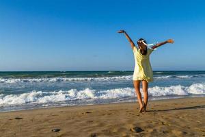 ung kvinna njuter av sin tid på en strand i skymningen
