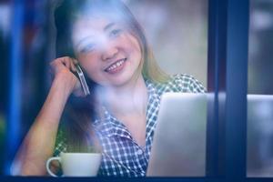 asien glad kvinna prata telefon i café och njuta av kaffe foto