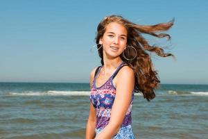 glad tjej med långt brunt hår njuter av den uppfriskande stranden. foto