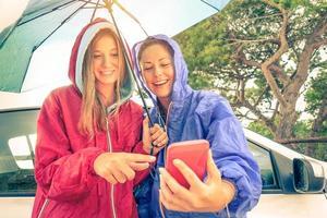 kvinnor bästa vänner njuter med smartphone med solen kommer ut foto