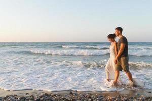 unga par tycker om att gå på en disig strand i skymningen foto