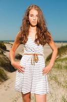 glad söt flicka med långt brunt hår njuter av stranden. foto