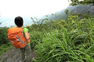 vandrare för ung kvinna njuta av det vackra landskapet vid bergstoppen foto