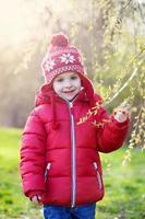 rolig liten pojke, njuter av solig vårdag i parken foto
