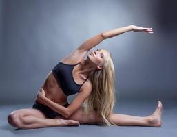 bild av leende ung kvinna som gör stretching foto