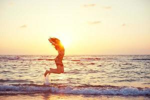 stilig tjej som hoppar i havet foto